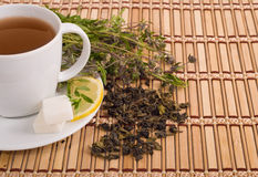 Green tea. With herbs and lemon on bamboo mat background Royalty Free Stock Photography