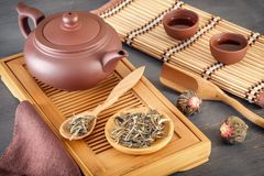 Green tea and attributes for tea ceremony - a ceramic teapot, cups, a strainer, chopsticks and tweezers are placed. On an old wooden table royalty free stock photo