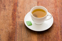 Green tea bag. Hot green tea in white cup and plate Royalty Free Stock Images