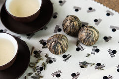 Green tea and balls bundle and Japanese style set cups. Small bowls of dry green tea leaves and small balls bundle of dried tea leaves on Japanese pattern stock photo