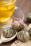 Green tea balls with flowers, tea cup and wooden spoon Royalty Free Stock Photo