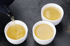 Green tea being poured into cups Royalty Free Stock Image
