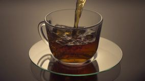 Green Tea being poured into glass tea cup stock footage