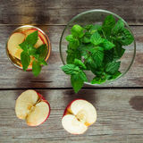 Green tea, a bowl with mint and cut apple Royalty Free Stock Photography