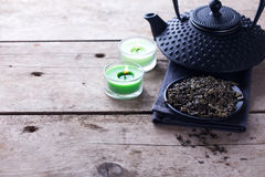 Green tea in bowl and traditional asian teapot  on aged wooden b Royalty Free Stock Photo