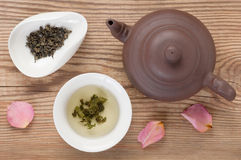 Green tea brewed in tea bowl served with tea tableware, top view on rustic wooden table decorated rose petals Royalty Free Stock Images