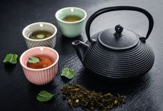 Green tea in cast-iron teapot Stock Photography