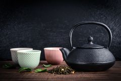 Green tea in cast-iron teapot. With small cups on black slate background Stock Image