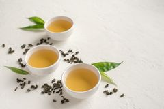 Green oolong tea. Green tea in ceramic cups, dry green oolong tea and tea leaves on white stone table, copy space royalty free stock photos