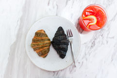 Green tea and charcoal croissants on a white dish with Srawberry Stock Photography