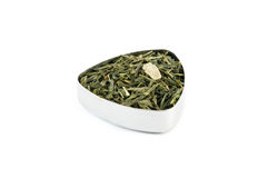 Green Tea. Chinese Sencha green tea mixed with pineapple and ginger, in a metal container Stock Photo