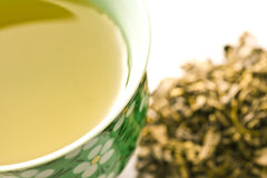 Green tea close up. Close-up of a cup with green tea and heap of green ten in the background stock photo