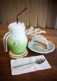 Green tea cool milk and tasty cake in coffee shop Royalty Free Stock Image