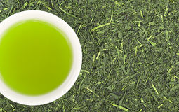 Green tea. Cup of green tea and green tea leaves background Stock Photos