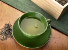 Green tea. In green cup with loose leaf Royalty Free Stock Photos