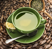 Green tea. In green cup with loose leaf Stock Photos