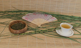 Green tea in a Cup, outdoor fan on bamboo Mat Royalty Free Stock Image
