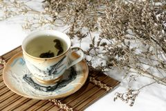 Green tea in a cup with a tea leafs. On white Royalty Free Stock Photo