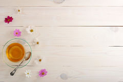Green tea with daisies in a clear glass mug. On rustic wooden white background and copy space for text menu - top view Stock Photo