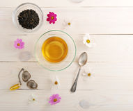 Green tea with daisies in a clear glass mug and tea strainer. For tea on rustic wooden white background and copy space for text menu - top view Royalty Free Stock Image