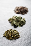 Green tea. Different sorts of green tea in a green cup Royalty Free Stock Photography
