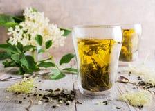 Green tea with elder flower. Healthy medicine green tea with elder flower in glass on old white wooden tafel with elder flower branches. Copy space Stock Photos