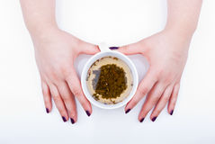 Green tea. Female hands holding a cup of natural green tea Royalty Free Stock Photos