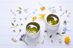 Herbal Tea Flowers Background Cup. Two cups of green tea on a white background with flowers Royalty Free Stock Images