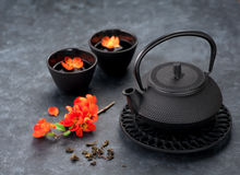 green tea and flowers. Black iron asian style teapot and cups Royalty Free Stock Photo