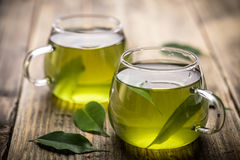 Green tea. Fresh green tea with tea leaves in the water Royalty Free Stock Image