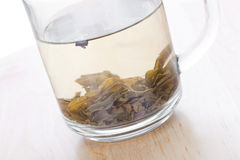 Green tea in glass cup with leafs on wooden table Stock Photography