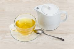 Green tea in glass cup on saucer, tea spoon, teapot. Green tea in a glass transparent cup on a glass saucer with tea spoon, white porcellaneous teapot on a light Royalty Free Stock Photography