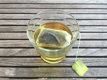 Green Tea. A glass of hot water with an infusing green tea sachet on a wooden surface table Royalty Free Stock Photo