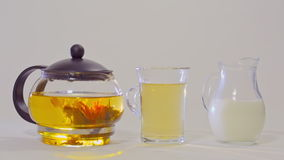 Green tea in a glass teapot, the tea in a transparent Cup and a  jug of milk. Green tea in a glass teapot, the tea in a transparent Cup and a small jug of milk stock video