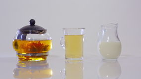 Green tea in a glass teapot, the tea in a transparent Cup and a  jug of milk. Green tea in a glass teapot, the tea in a transparent Cup and a small jug of milk stock footage