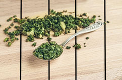 Green tea in an iron spoon on wooden Stock Image