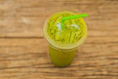Green tea latte with ice in plastic cup and straw on wooden background. Homemade Iced Matcha Latte Tea with Milk take. Away royalty free stock photography