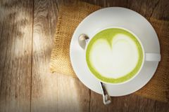Green tea latte on wood background. A cup go green tea latte on wood background with vintage tone Stock Images