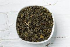 Green tea leaves gunpowder in white bowl on wooden background. Royalty Free Stock Photo