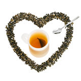 Green tea leaves in heart shape with cup of tea Royalty Free Stock Photo