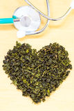 Green tea leaves heart shaped and stethoscope Royalty Free Stock Photo