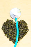 Green tea leaves heart shaped and stethoscope Royalty Free Stock Photos