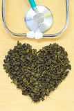 Green tea leaves heart shaped and stethoscope Royalty Free Stock Photography