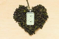 Green tea leaves heart shaped and watch Stock Photo