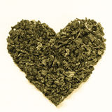 Green tea leaves heart shaped on wooden surface Stock Photos