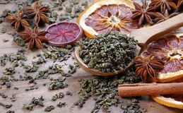 Green Tea Leaves In A Wooden Spoon, Dried Citruses, Cinnamon And Anise. Tea And Spices Royalty Free Stock Image