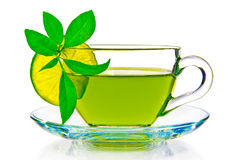 Green tea with the leaves of a lemon on a white background.  Royalty Free Stock Photos