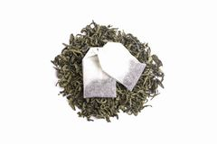Green tea leaves and sachets of black tea isolated on white background Royalty Free Stock Photo
