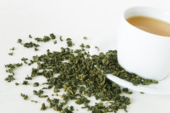 Green tea leaves and white cup Stock Photos