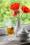 Green tea with lemon and mint in a glass mug and poppies in a white vase Royalty Free Stock Images